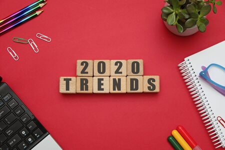 2020 trends concept - flat lay composition with wooden cubes at office workspace on red table