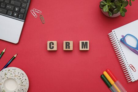 CRM concept - flat lay composition with wooden cubes at office workspace on red table Stockfoto