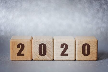 2020 new year concept: wooden cubes on silver background with beautiful bokeh