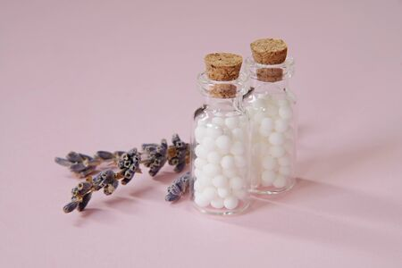 Homeopathic globules and glass bottle close up on pink background. Alternative Homeopathy medicine herbs, healthcare and pills concept. copyspace for text.