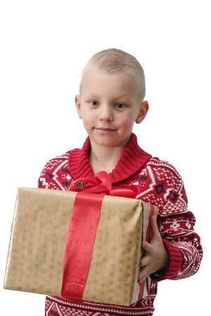 Child holding Christmas gift box in hand. Boy Isolated on white background. New year and x-mas concept. 免版税图像