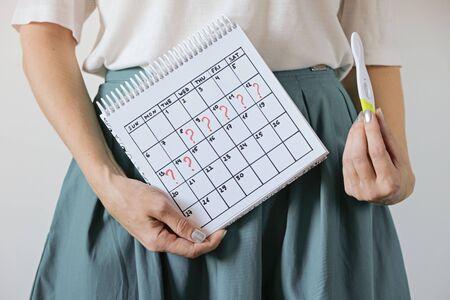 Frau, die Kalender mit markierter verpasster Periode und Schwangerschaftstest hält. Ungewollte Schwangerschaft und Verzögerung der Menstruation.