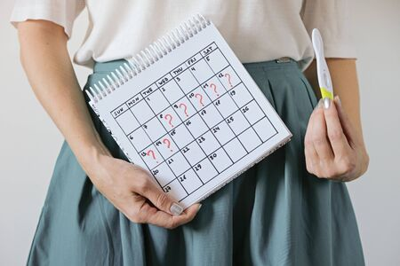 Woman holding calendar with marked missed period and pregnancy test. Unwanted pregnancy and delay in menstruation.