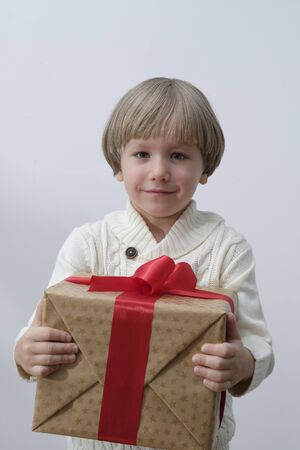 Child holding Christmas gift box in hand. Boy on white background. New year and x-mas concept.