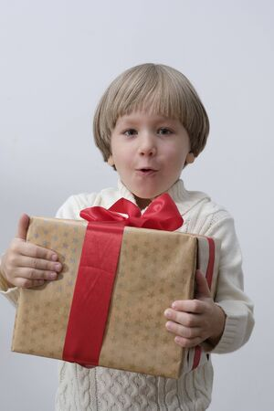 Surprised child holding Christmas gift box in hand. Boy on white background. New year and x-mas concept. Stock fotó