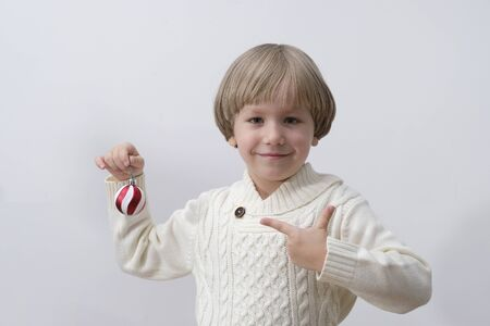 Child holding Christmas decoration in hand. Boy on white background. New year and x-mas concept.