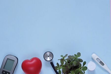 Doctor medicine flat lay: stethocrope, termometer, flower, heart on blue background Stockfoto