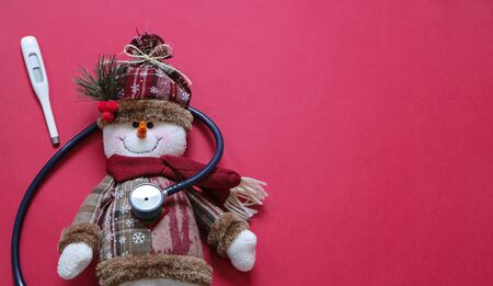 Doctor and christmas concept. Ill snowman and stethoscope on red background with place for text.