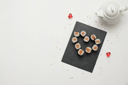 Sushi for Valentines Day - roll in heart shape, on plate on . Flat lay