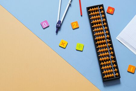 Old abacus with school supplies, drawing compass, numbers on beige background . Mental mathematics, math concept. Stock fotó