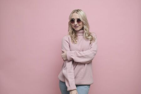 Happy coquettish woman face with blond hair in glasses and wool sweater on pastel pink background. Close up Reklamní fotografie