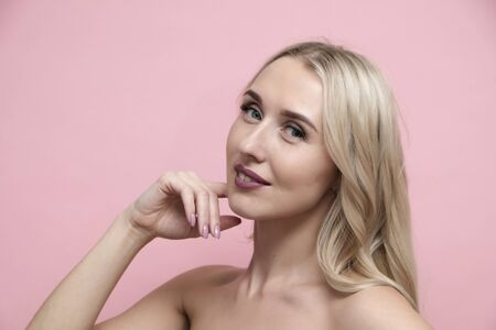 Beautiful blond woman with naked shoulders on pastel pink background. Beauty, cosmetics and skin care concept