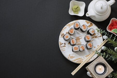 Order delivery japanese food sushi rolls while you stay at home on quarantine. House shape on black background with copy space