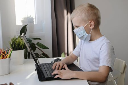 Distance learning online education. Cute caucasian boy doing homework with laptop at home while quarantine of epidemia corona virus