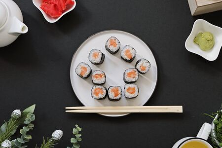 Order delivery japanese food sushi rolls while you stay at home on quarantine. House shape on black background Imagens