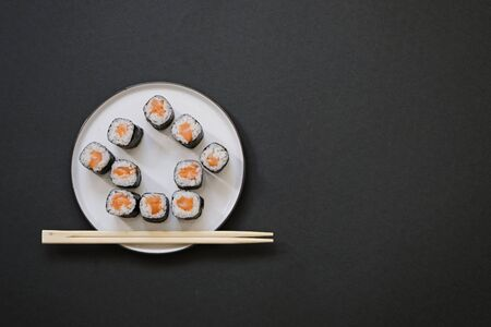 House shaped sushi rolls with chopsticks on black background with copy space