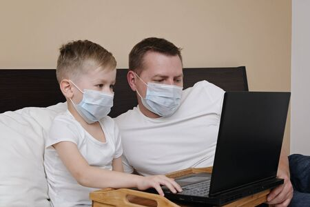 Father with kid and laptop in protective mask lying on the bed while quarantine of corona virus. Distance education, stay at home