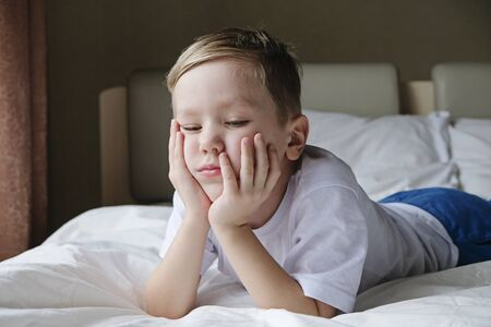 Unhappy offended little boy sitting alone on the bed. Loneliness, naughtiness concept Imagens
