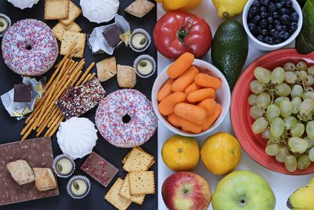 Healthy and unhealthy food concept, fruits and vegetables vs donuts, sweets and chocolate with womans hand. Top view