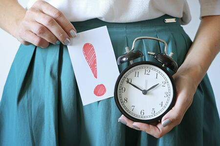 Woman holding clock at belly. Missed period, unwanted pregnancy, womans health and delay in menstruation. Imagens