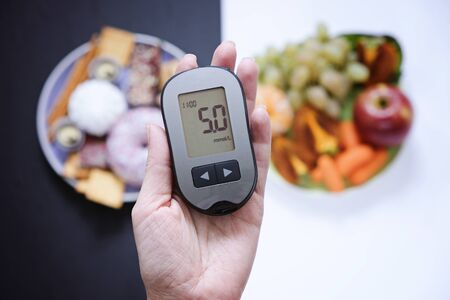 Diabetes concept: sweets and unhealthy food with glucometer. Nutrition cause diabetic desease
