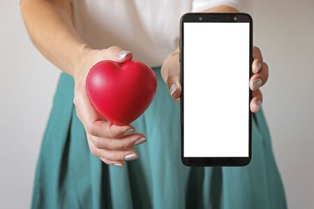 A womans hands holding a heart symbol on belly and smartphone. Application for womans health, gynecology
