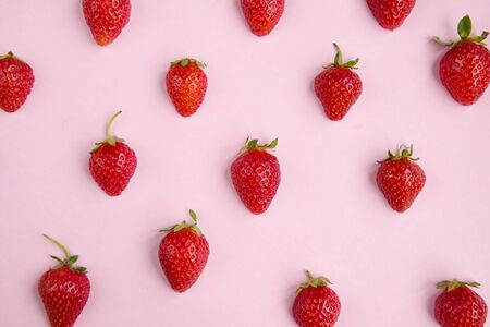 Pink background with fresh strawberry halves, top view Imagens