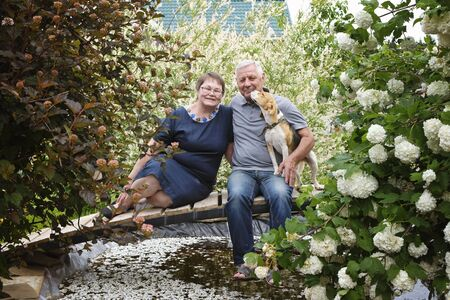 Happy senior couple - mature man and woman at their house, with dog pet Imagens