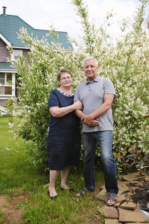Beautiful senior couple - mature man and woman at their house, outdoors Imagens