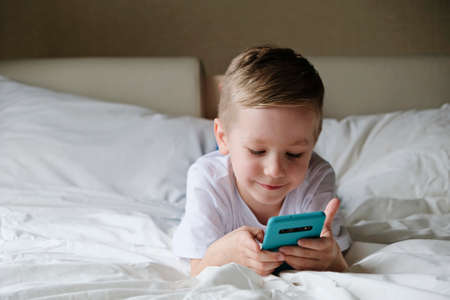 Cute little boy toddler playing mobile game, lying on a bed and holding smartphone Imagens - 151002121