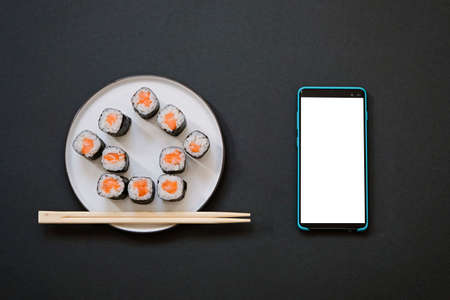 House shape sushi rolls with chopsticks and smartphone on black background with copy space