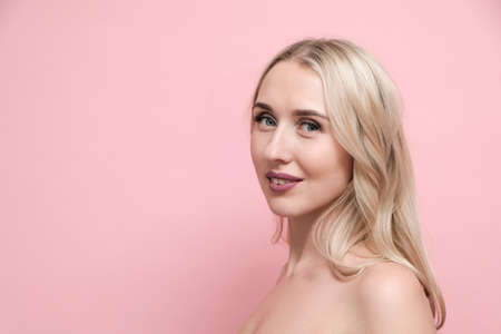 Beautiful blond woman with shoulders on pastel pink background. Beauty, cosmetics and skin care concept