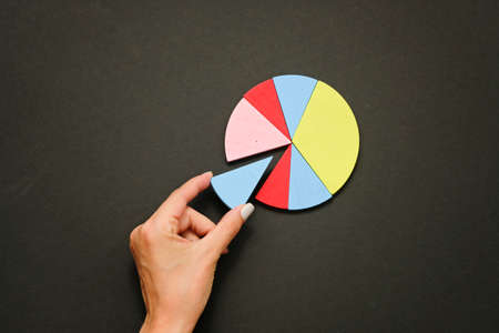 Colorful fraction circles arranged into a circle graph and hand, black background.