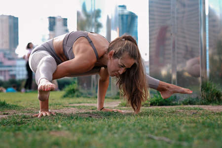 Young woman doing yoga exercises with city on background. Beautiful asana on hands Imagens