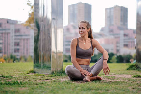 Young woman doing sittinh in yoga pose with city on background. eka pada kaundiniasana Imagens
