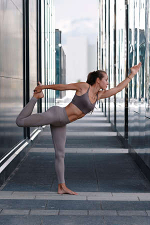 Young woman doing yoga exercises with city on background. Beautiful asana Imagens - 153273654