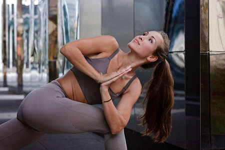 Young woman doing yoga exercises with city on background. Beautiful asana