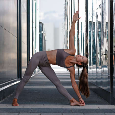 Young woman doing yoga exercises with city on background. Trikonasana Imagens