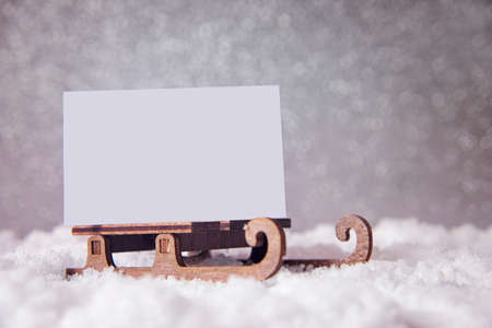 Christmas card on a sled on snow. Glitter festive background