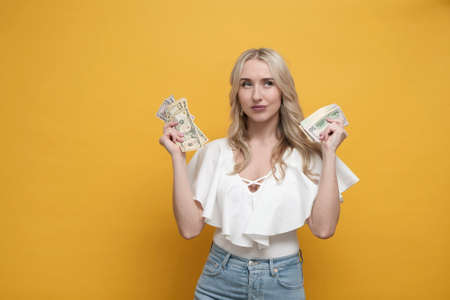 Happy blond woman holding pack of dollars, thinking about shopping or expenses over yellow background. Copy space Imagens - 154614403