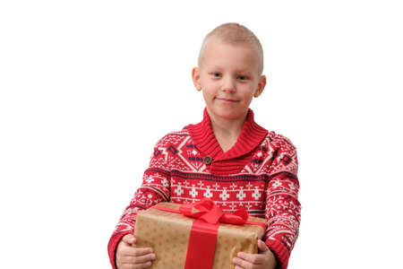 Child holding Christmas gift box in hand. Boy Isolated on white background. New year and x-mas concept. Imagens