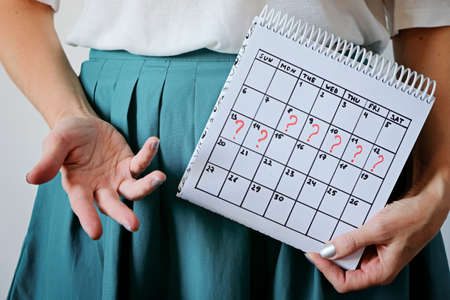 Woman holding calender with marked missed period. Unwanted pregnancy, womans health and delay in menstruation. Imagens
