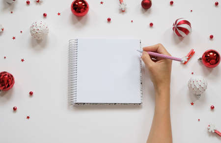 Goal lift for New Year. Holiday decorations and notebook with clean note book on white table, flat lay style. Planning concept. Imagens