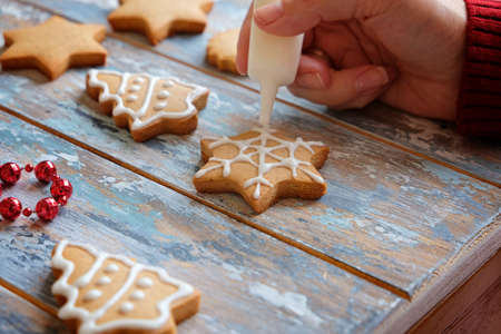 Making christmas ginger cookies with white glaze decoration, close up