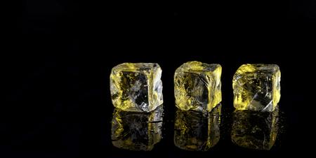 three yellow ice cubes on black background