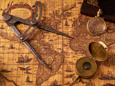 Old vintage retro compass on ancient world map. Vintage still life. Travel geography navigation concept background.