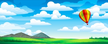 Colored balloon on a blue cloudy sky and green meadow with mountains and forest