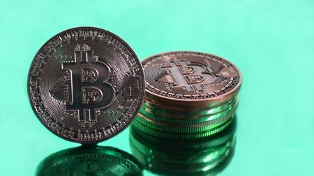 Bitcoin coins closeup on green background