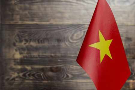 Fragment of the flag of the socialist Republic of Vietnam in the foreground blurred wooden background copy space