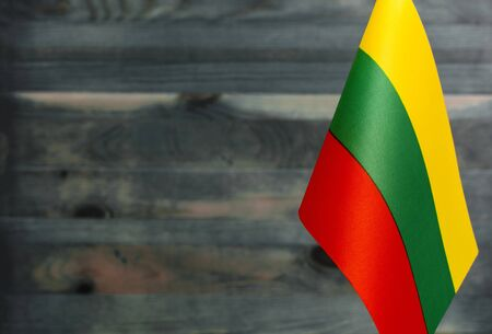 Fragment of the flag of the Republic of Lithuania in the foreground blurred wooden background place under the text 版權商用圖片